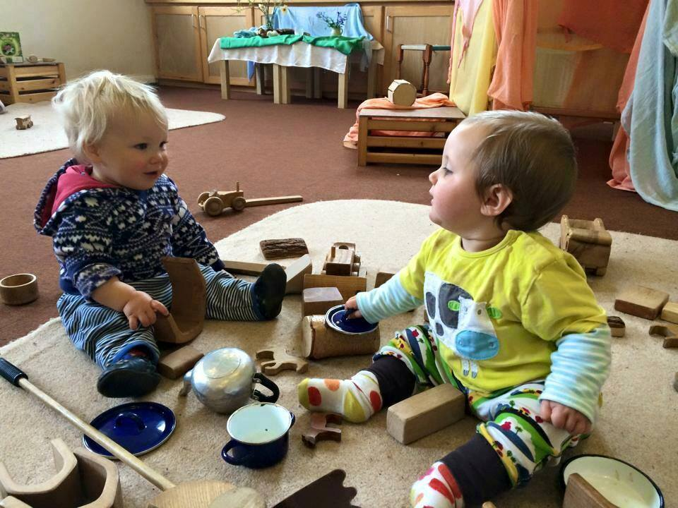 picture of two toddlers sitting on a rug playing with wooden bricks and and play kitchen toys