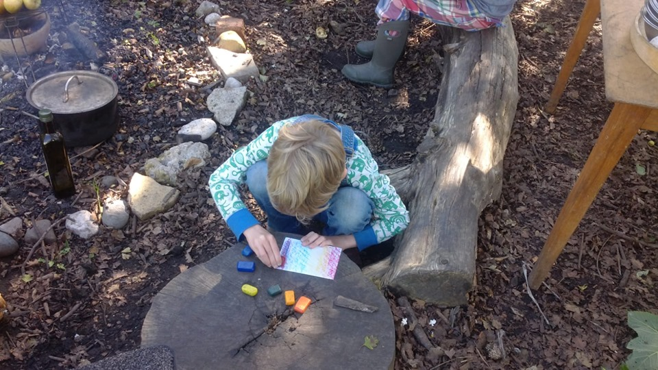child using a tree stump as a table to do some colouring.