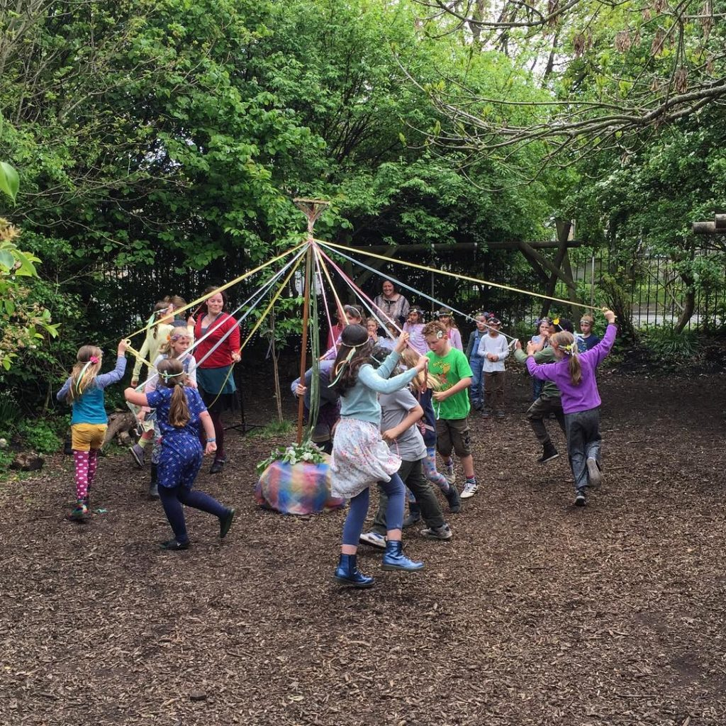 picture of pupils may pole dancing in the school garden, wearing woven garlands on their heads which they made
