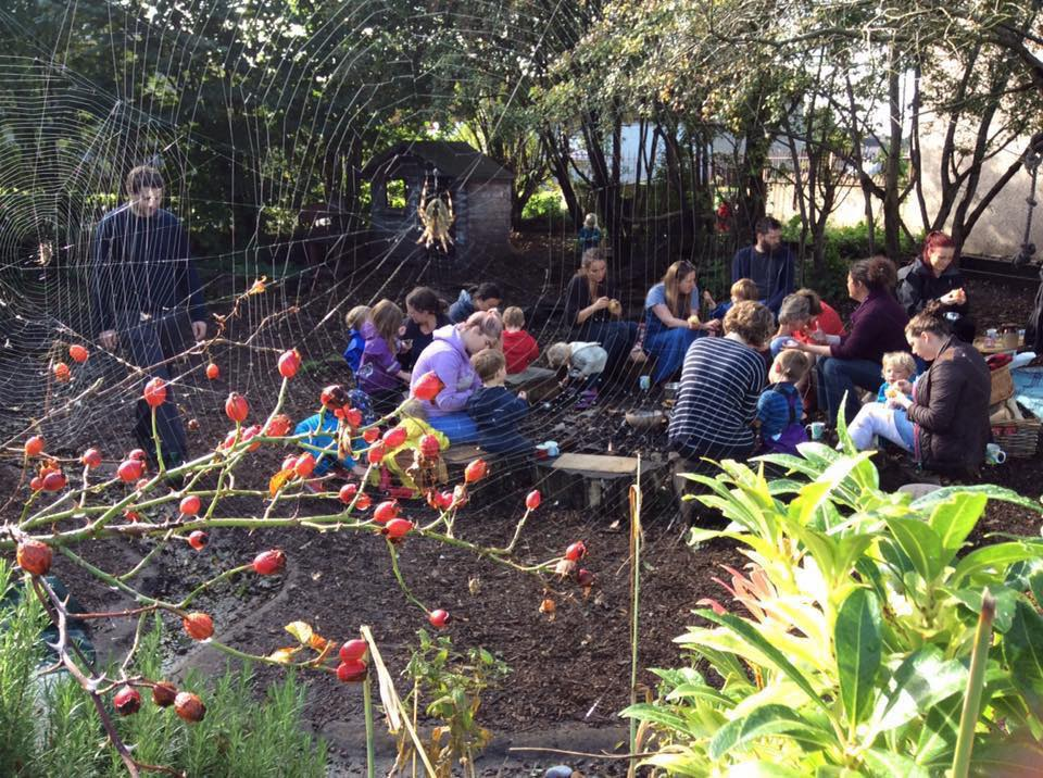 picture of parents and toddlers sitting on tree stumps around a camp fire in the school garden